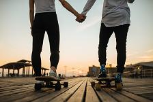 スケボーをしながら手をつなぐカップル