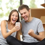 Euphoric couple sitting on the floor moving house and watching smart phone