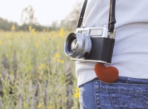Young  woman  photographer with retro camera and red Heart in flower garden,warm tone vintage.