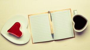 Coffee cup jelly cake in form of heart and paper blank notebook with pen on desk, top view copy space for text