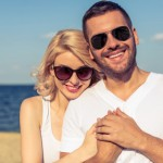 Portrait of beautiful young couple in sun glasses hugging, looking at camera and smiling, sunny seaside in the background